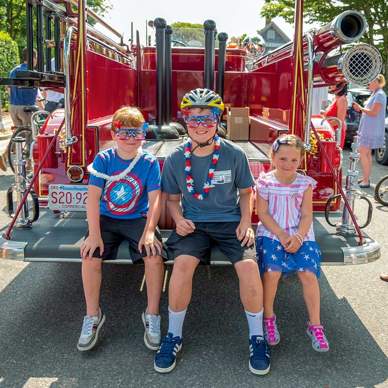Three children sitting on the back of an antique fire truck.