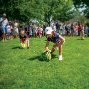 Child rolling a watermelon.