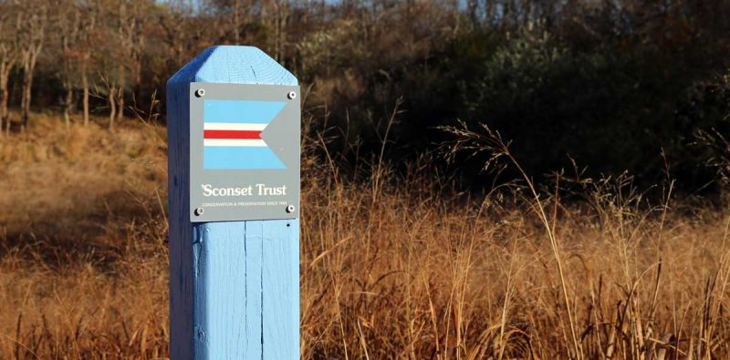 Blue Sconset Trust trail marker post with brown grass in the background
