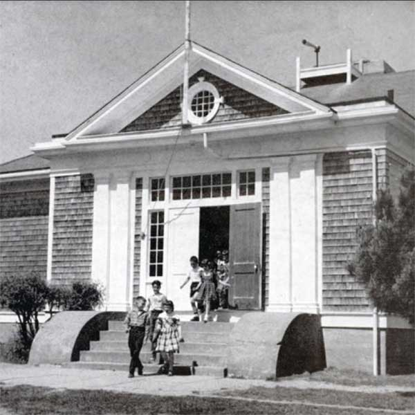 Black and white of children coming out of a  school house.