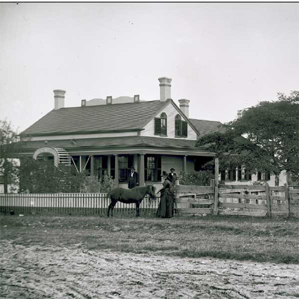 Black and white image of a horse and woman standing in front of a house.